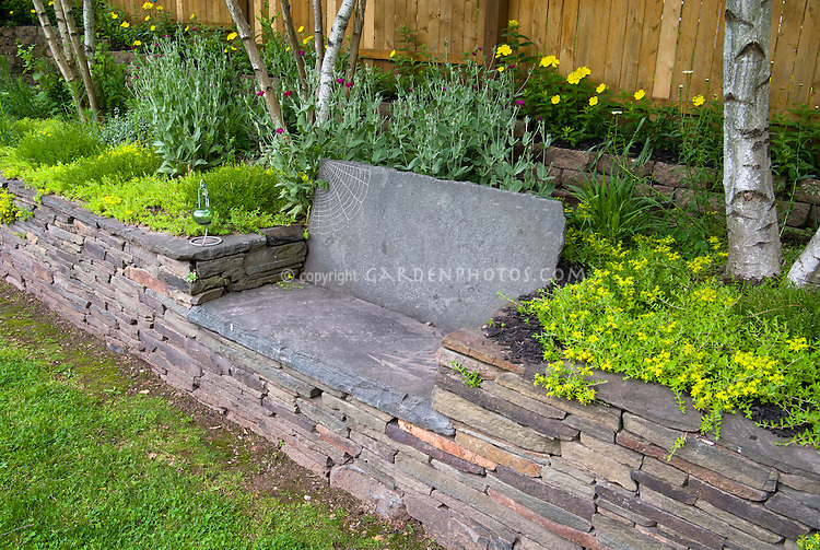 Etched artistic stone garden bench in raised bed stone wall, fence, birch trees, sedum groundovders, flowers and perennials, lawn grass
