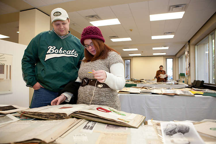 From left: Ohio University 2012 alumnus Kevin Powell, of Mason, Ohio, and Elizabeth Bowman, of Harrisville, Ohio, peruse materials from the Ohio University Archives collections, which were on display on the fourth floor of Alden Library for Homecoming Weekend on Saturday, Oct. 13, 2012. (Photo by Lauren Pond/Ohio University Libraries)