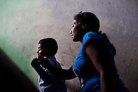 Razia Shabnam (in blue) and son walk up to their home in Ekbalpore after picking her son, Saihaan, up from the St. Thomas School in Kidderpur after finishing her boxing training sessions in Calcutta, West Bengal, India. Razia Shabnam, 28, was one of the first women boxers in Kolkata. She was also the first woman in her community to go to college. She is now a coach and one of only three international female boxing referees in India.  Photo by Suzanne Lee for Panos London