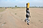 A woman in Yei, Southern Sudan, walks home after getting water from a well provided by the United Methodist Committee on Relief (UMCOR).