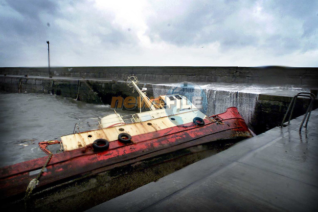 A trawler lying on it's side in Clogherhead on Monday morning.Picture: Paul Mohan/Newsfile