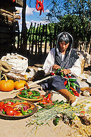 Dressed in Spanish Colonial garb, Virginia Vigil ties chile peppers into a string called a ristra at the Los Golondrinas Historic Museum's Fall Festival in October near Santa Fe