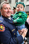 "March 16, 2013 - New York, NY, U.S. - Nassau County Police Officer holidng young boy in green who's wearing ""Get Luck Be Irish"" button, shortly before marching in the 252nd annual NYC St. Patrick's Day Parade."