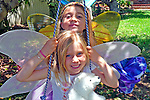 Two young girls swing with fairy wings for creative play fun.
