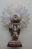 Monumental sun monstrance in silver, gems and wood, early 18th century, from the Convento do Sacramento de Alcantara, Lisbon, in the Museu Nacional de Machado de Castro, Coimbra, Portugal. The angel holds a sphere from which radiates a corona of silver rays with the host box in the centre, mounted over a circular plate with 8 silver-gilt cherubs. The museum was opened in 1913 and renovated 2004-2012. The city of Coimbra dates back to Roman times and was the capital of Portugal from 1131 to 1255. Its historic buildings are listed as a UNESCO World Heritage Site. Picture by Manuel Cohen