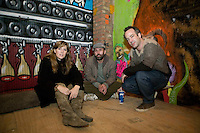 15 December 2006 - New York City, NY - Curators (LtoR) Sara and Marc Schiller and Malcolm Stevenson pose for the photograph among artwork exposed in a three-day street art exhibition held inside a 19th-century brick building at 11 Spring Street in the NoLIta neighborhood of New York City, USA, 15 December 2006. The building's new owners, Caroline Cummings and Bill Elias, called on the Wooster Collective to curate the show as a last hurrah for a site that long served as a canvas for street art.<br />