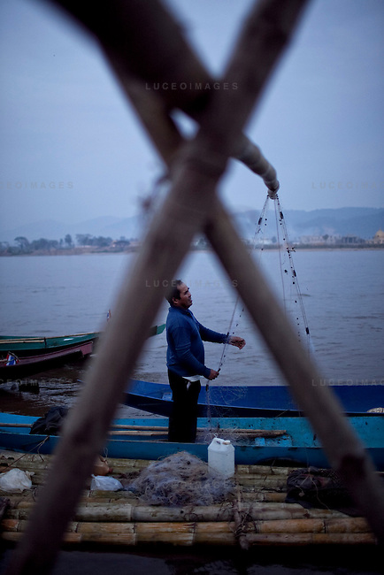 "Nil, 52, organizes his fishing net after fishing on the Mekong River in Sop Ruak, Thailand. He says that prices in town keep getting hirer as development increase.  But the fish are few in numbers and the water low in inconsistent due to the dams in China he said. ""I wish it was like 7-8 years ago when there were a lot more fish,"" he said. Photo taken on Thursday, December 10, 2009. Kevin German / Luceo Images"