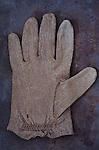 Victorian childs beige cotton glove lying palm up on rusty metal sheet