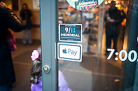 Signage in a Whole Foods Market in New York informs customers of their acceptance of the Apple Pay method of payment, seen on Saturday, November 15, 2014. The three major retailers that accept the mobile payments, McDonald's, Walgreens and Whole Foods have reported an increase in mobile payments since the introduction of Apple Pay. (© Richard B. Levine)