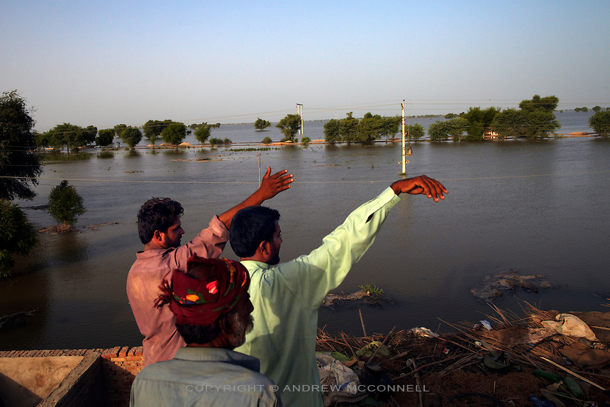 Men gesture from a rooftop near Bubak, Sindh province, Pakistan. Flood water inundated the surrounding area after Manchar Lake burst its banks. Officials made a breach in the lake's embankments to direct water away from the nearby cities of Dadu and Sehwan, in Sindh Province, Pakistan.