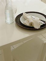 The glossy finish of this kitchen table highlights the dark raffia underplate of this monochrome place setting