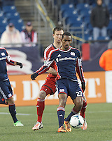 New England Revolution forward Jerry Bengtson (27) passes the ball as Toronto FC defender Steven Caldwell (13) pressures. In a Major League Soccer (MLS) match, the New England Revolution (blue) defeated Toronto FC (red), 2-0, at Gillette Stadium on May 25, 2013.