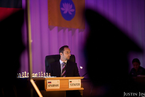 Police watch world chess champion Veselin Topalov facing an empty chair during one of the most important chess matches in history. ..Topalov, a Bulgarian ranked first according to Fide, is playing against Kramnik, who is the Classical Chess World Champion, a title established after Garry Kasparov led a breakaway from Fide in 1993. The two grandmasters, both aged 31, are competing for the right to be undisputed world chess champion..Kramnik, a Russian, did not show up for the fifth game and threatened to withdraw from the match after he was accused of cheating and locked out of his private bathroom. .Kramnik had been leading Topalov 3-1 after four games in the 12-game match. But Kramnik boycotted game five, angered by an Appeals Committee decision to lock the private bathrooms for both players and insist that each use a common bathroom for the rest of the match. Topalov was also unhappy with the decision; his manager said it would not prevent Kramnik from cheating since he would still be alone in the lavatory..The match is hosted by FIDE President Kirsan Ilyumzhinov. ..The match beginning September 21 in Elista, the capital of Europe?s only Buddhist nation, will end a 13-year split in the game that has produced rival claims to the title. ..A Buddhist millionaire businessman, Ilyumzhinov acquired his wealth in the economic free-for-all which followed the collapse of the Soviet Union. ..At the age of just over 30, he was elected president in 1993 after promising voters $100 each and a mobile phone for every shepherd. Soon after, he introduced presidential rule, concentrating power in his own hands. ..He denies persistent accusations of corruption, human rights abuses and the suppression of media freedom. When Larisa Yudina, editor of the republic's only opposition newspaper and one of his harshest critics, was murdered in 1998, he strenuously rejected allegations of involvement. ..Mr Ilyumzhinov has been president of the International Chess Federation (FIDE) since 1995
