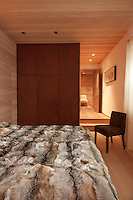View over a double bed covered in a fur throw towards a wall of built-in cupboards