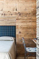 Built-in cupboards are concealed in the rough wood panelling in one of the guest bedrooms