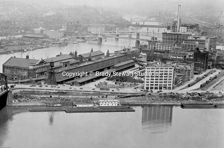Pittsburgh PA:  View of the Point Buildings in 1928.  In the background are the new 7th & 9th Street bridges;  self-anchored suspension bridges spanning the Allegheny River.  Company signs are the city buildings include:  Victor Radio, Demmler & Schenck, Mackintosh Hemphill Company, Daugherty Company Canned Foods, Imperial Power Building, Union Electric Company, General Electric Wiring Systems, Pittsburgh Wharf and Terminal Company, Lent Traffic Company, Wheeling Steel Corporation Harbor, and the Alling & Cory Company