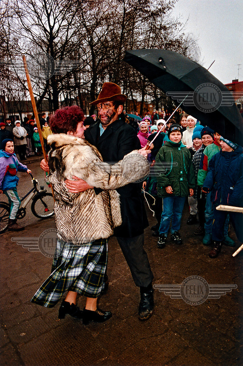 """Two participants dance in the street. The """"Decapitation of Death"""" takes place in the small town of Jedlinsk, in central Poland, every year on the Tuesday before Lent (Shrove Tuesday). Its exact origins are unclear, but it is believed to have begun in the 16th Century, and was first written by the local rector in 1839. The whole town gets involved in the theatrical pageant, and the words uttered by the main players, the Bride, Angel, Jew, Hangman, Devil and Bartholomew the Policeman, are well known among locals. It is believed that on this day Death gets drunk and loses its scythe, offering the perfect opportunity for him to be arrested and executed. After calls from the crowd, Death is sentenced to death, and a grand feast, marking the beginning of Lent, can begin."""