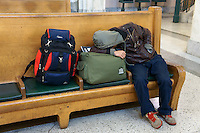 Sleeping male traveler on a wooden bench, Pacific Central Railway Station, Vancouver, British Columbia, Canada