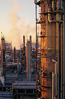 worker on petrolium refinery stack at sunrise
