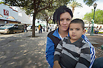 """Anaivis Machado, a psychologist, and her 3-year old son Dario sit in the Plaza Benito Juarez in Nuevo Laredo, Mexico, on March 3, 2017. They left their home in Santa Clara, Cuba, bound for the United States, but are now waiting close to the U.S.-Mexico border, caught in limbo by the elimination in January of the infamous """"wet foot, dry foot"""" policy of the United States. They are not allowed to enter the U.S. yet don't want to return to Cuba. Many of the city's churches have become temporary shelters for the immigrants, and congregations rotate responsibility for feeding the Cubans. Such solidarity from ordinary Mexicans is being tested these days, as not only are the Cubans stuck at the border, but the U.S. has stepped up deportations of Mexican nationals, while at the same time detaining many undocumented workers from other nations and simply dumping them on the US-Mexico border. Machado's husband is a member of the Methodist Church in Cuba."""