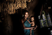 Mahari Usenti is seen with her little child inside her hut in Godhari village in Orcha block of Chattisgarh, India. Photo: Sanjit Das