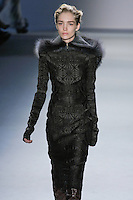 Janice Alida walks runway in a dark green vault jacquard long sleeve sheath dress with oversized charcoal raccoon detachable hood from the Vera Wang Fall 2012 Vis-a-gris collection, during Mercedes-Benz Fashion Week Fall 2012 in New York.