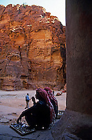 Two Bedouins sitting at the entrance to El Khazneh Treasury, Petra, Jordan.