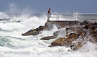 A man stands on the jetty and looks out at the heavy surf generated by Hurricane Irene, Ponce Inlet, FL, Thursday, August 25, 2011.   (Photo by Brian Cleary/www.bcpix.com)
