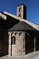 Low angle view of a semi-circular apse with the four storeys bell tower in the background, Santa Maria de Taull Church, 1123, consecrated by Ramon Guillem, the bishop of Roda, Taull, Province of Lleida, Catalonia, Spain. The church was built with three naves, each ending with an apse which cornice is decorated with Lombard arches. The bell tower is the oldest part and it is also decorated with Lombard arches and mullioned windows. The church was heavily renovated in the 18th century, its frescoes were moved to MNAC in around 1918. Santa Maria de Taull Church is part of the Catalan Romanesque churches of the Vall de Boí which were declared a World Heritage Site by UNESCO in November 2000. Picture by Manuel Cohen