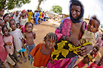A Wodaabe Fulani woman and children from Niger visit the market area of a village near Abuja, Nigeria.  The Fulani are traditionally pastoralists, criscrossing the Sahel and Sahara in search of water and green pastures.
