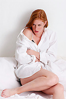 Young red haired woman sitting in bed with bare legs
