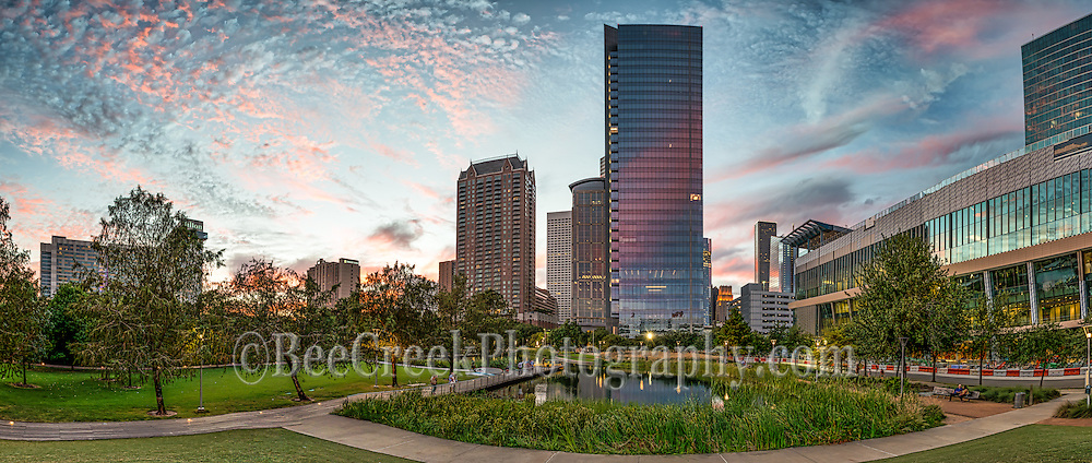 This is a pano of the Discovery Green Park in downtown Houston just as the sun is being to set.  The reflective high rise has picked up the pink colors in the sky as the sun sets over the cityscape of this modern urban environment. Watermark will not appear on image