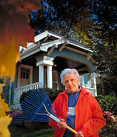 Portrait of an elderly woman in front of her house holding a rake.