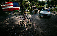 A young boy on a bicycle rolls through the campgrounds on a Fourth of July celebration along the St. Marys River.
