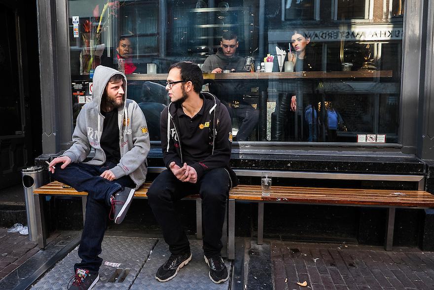 Nederland, Amsterdam, 8 maart  2015<br /> Jongelui zitten buiten voor een kroeg te roken.<br /> <br />  <br /> Foto: (c) Michiel Wijnbergh