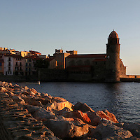 Eglise Notre Dame des Anges, and village houses, Collioure, France, with the rocky shoreline in the foreground. The bell tower was converted from a medieval lighthouse and the Mediterranean Gothic style nave was built in 1684. The dome was added to the bell tower in 1810. Picasso, Matisse, Derain, Dufy, Chagall, Marquet, and many others immortalized the small Catalan harbour in their works. Picture by Manuel Cohen.