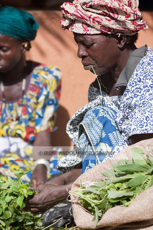 In the town of Djibo in northern Burkina Faso, a woman sells vegetables in the market.