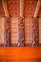 Carved Traditional Maori Figure, called Poupou, supporting the overhead rafters of the meeting house.  These are the 12th, 13th, and 14th on the left side after entering the house.  The twelth and thirteenth represent the style of the Ngati Porou tribe of the east coast north of Gisborne; the 14th represents the Rongowhakata tribe of Gisborne.   Te Whare Runanga, built 1940, Waitangi Treaty Grounds, Paihia, north island, New Zealand.  The woven panels on either side of the poupou are called tukutuku.  These are comprised of vertically-placed toetoe reeds (kakaho) across which lie narrow laths (kaho), laced through with colored strips of pingao grass and kiekie.