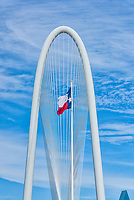 This is a verticle capture of the arch of the Margaret Hunt Hill bridge with the Texas Flag flying is which is unique to Dallas Texas.