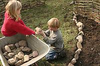 Kinder legen eigenes kleines Gemüsebeet an, Umrandung mit Feldsteinen, abgegrenzt durch einen Weidenzaun aus Weidenzweigen, Beet, Garten