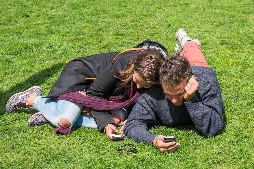 Nederland, Amsterdam, 30 mei 2015<br /> Museumplein. Stelletjes liggen in het gras van het Museumplein. Toeristen zijn moe van het slenteren door de stad. Beiden checken hun smartphones voor berichten.<br /> <br /> Foto: Michiel Wijnbergh