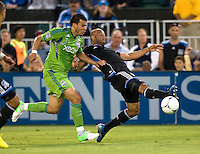 Victor Bernardez of Earthquakes kicks the ball away from Sounders defender during the game at Buck Shaw Stadium in Santa Clara, California on August 11th, 2012.   Earthquakes defeated Sounders, 2-1.