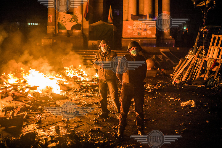 Two protesters stand amid the burning detritus near Maidan Nezalezhnosti (Independence Square), renamed EuroMaidan by protesters since November 2013 during an anti government protest. Protests against the government of President Viktor Yanukovych were sparked on 21 November 2014 by the Ukrainian government's decision to suspend preparations for the signing of an association agreement with the European Union that would have increased trade with the EU. Some believe that the U-turn came about as a result of pressure from President Putin of Russia who wants Ukraine to join a customs union with itself, Kazakhstan and Belarus. Russia offered 15 billion dollars of soft loans and reduced price gas to Ukraine at the same time as discussions with the EU were taking place. After weeks of protests and a number of deaths, Prime Minister Mykola Azarov and the entire cabinet resigned. Protesters are holding out, however, for President Yanukovych to resign and continue to occupy public buildings and squares to put pressure on the president. On 18 February, after Yanukovych's party scuppered a move to change the constitution to reduce the powers of the president, renewed fighting between protesters and police broke out and had cost the lives of around 80 people by Friday 21st February.