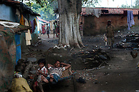 A man resting outside his house at Kujama slum area. The authorities have put up a notice to evacuate the slum as the coal mine fire has already entered the slum village. A huge coal mine fire is engulfing the city of Jharia from all its sides. All scientific efforts have gone in vain to stop this raging fire. This fire is affecting lives of people living in and around Jharia. Jharkhand, India. Arindam Mukherjee