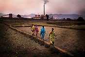 Women walk past a field against the background of Vedanta plant in Ijirupa village in Lanjigarh, Orissa, India. The huge bauxite deposits in Niyamgiri have led the Vedanta group to set up an alumina refinery at Lanjigarh, making the tribals apprehensive about their habitat. The UK based Vedanta Resources  has come under immense pressure from human rights and environmental groups to abandon its plans to mine at the Niyamgiri mountains in Orissa for bauxite (to extract aluminium). The dig site is considered a sacred ground by the local Dongria Kondh community and has attracted support from conservationists from across the world.
