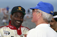Walter Payton, left, talks with Paul Newman at the Nissan World Challnge IMSA race, Florida State Fairgrounds, September 1990. (Photo by Brian Cleary/www.bcpix.com)