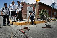 06/02/2010..High-School students pour dirt to cover the blood of a victim who was shot and killed in front of their school in downtown Ciudad Juarez.
