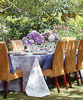 A dining table with wicker chairs arranged for lunch in the garden