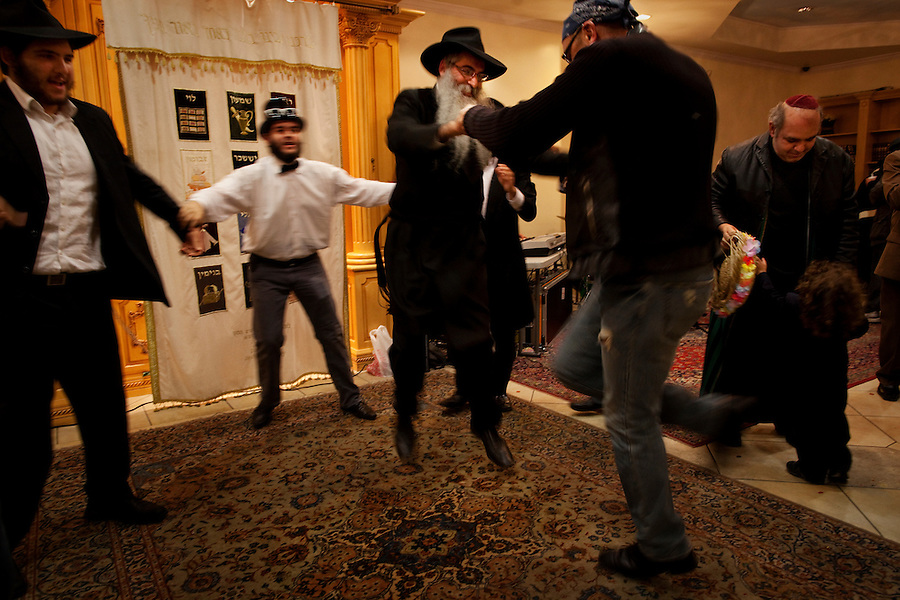 Los Angeles, California, March 19, 2011 - Members of the Chabad Persian Youth Center celebrate Purim by dancing after the reading of the Megillah at the center...Purim is a Jewish holiday that commemorates the deliverance of the Jewish people living in the Persian Empire from genocide at the hands of the political advisor, Haman, to the Persian King Ahasuerus, as documented in the Talmud's Book of Esther. It is celebrated by the reading of the Scroll of Esther or the Megillah, sending food gifts to friends, giving charity to the poor and celebrating with a festive meal. During the reading of the Megillah, when Haman's name is mentioned (which happens 54 times) the congregation engages in loud roars and the use of rattles in an effort to blot out his name. Today children and some adults dress in costume and masquerade to celebrate Purim. The custom is believed to have originated during the 15th century by Italian Jews influenced by the Roman carnival. One idea for the costumes is that God disguised his presence behind many of the natural events that happened during Purim. .