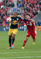 Toronto, Ontario - May 17, 2014: New York Red Bulls forward Thierry Henry #14 battles for a ball with Toronto FC midfielder Jonathan Osorio #21during the second half in a game between the New York Red Bulls and Toronto FC at BMO Field. Toronto FC won 2-0.